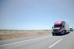 Semi convoy de camiones en la carretera recta en meseta plana fotografía de archivo