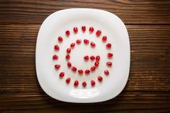 Semi del melograno nella forma di lettera G sul piatto bianco su w rustico immagini stock