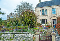 Semi-detached stone built house in Yorkshire Dales. Semi-detached stone built house in Grassington, Yorkshire Dales with colorful garden and steps down to gate stock images