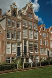 Semi-detached typical houses and green garden at Begijnhof, a medieval semi-monastic community in Amsterdam. stock images