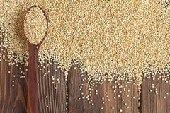 Semi di Kinoa in cucchiaio di legno sulla tavola di legno, organica Immagine Stock Libera da Diritti