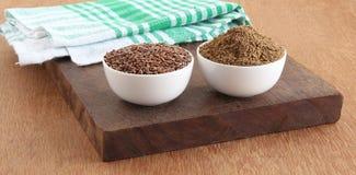 Semi di lino dell'alimento e polvere sani dei semi di lino in ciotole sul bordo di legno Fotografia Stock