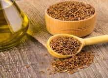 Semi di lino e olio di semi di lino di Brown su una superficie di legno Immagine Stock