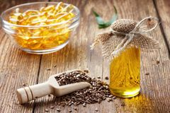 Semi di lino ed olio in bottiglia su fondo di legno immagini stock