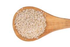 Semi di sesamo con il cucchiaio di legno su un fondo bianco Fotografie Stock Libere da Diritti