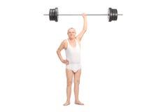 Semi-dressed senior lifting a heavy barbell Stock Photo