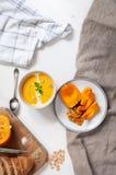 Semi e verde di zucca cremosi del soupwith della zucca, pane con crusca e zucca affettata sul fondo del tessuto e di legno top fotografia stock