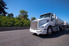 Semi el camión con dos remolques del tanque lleva el combustible en el camino imagen de archivo