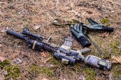 Semi espingarda automática e luvas táticas na terra na floresta Fotografia de Stock Royalty Free