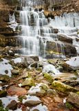 Semi frozen waterfall Tupavica thundering in cascades down the red cliff royalty free stock photos