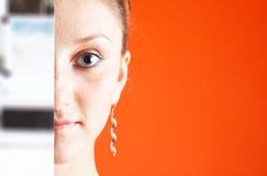 Semi-hidden Face 2. A young woman stands behind a reflective metallic sheet, reveal half her face. She stares directly into the camera with her eye wide open Royalty Free Stock Image