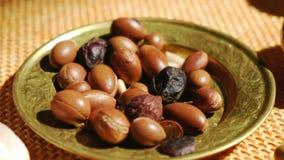 Semi matti dell'argania spinosa su un piatto - l'argania spinosa è utile come antiossidante per le smagliature curative della pel stock footage