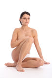 Semi naked young woman sitting hand over breasts Stock Images