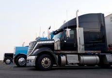 Semi os caminhões modernos e clássicos comerciais na parada de caminhão alinham Fotografia de Stock