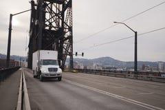 Semi poder moderno de la clase del midle del camión en el puente viejo en abajo la ciudad P Fotos de archivo