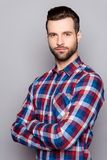 A semi portrait of serious young freelancer in checkered shirt s. Tanding with crossed hands against gray background stock photography