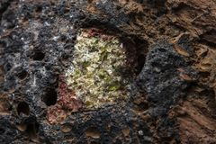 Semi-precious stone olivine in basalt. Olivine is a semi-precious stone found in basalt rocks on lanzarote one of the canary islands stock photos