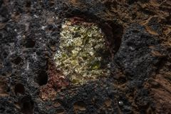 Semi-precious stone olivine in basalt. Olivine is a semi-precious stone found in basalt rocks on lanzarote one of the canary islands stock photography