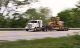 Semi pulling heavy machinery blur Royalty Free Stock Photo