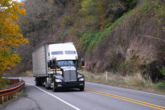 Semi reboque preto e branco da japona do caminhão na estrada do outono Fotografia de Stock