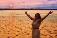 Semi Silhouette of Woman Raising Hands at Ocean. Semi silhouette of a woman raising her hands in worship at sunset at the ocean Stock Photo