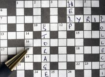 Semi solved crossword puzzle with pen. A pen on a crossword which has some clues solved Royalty Free Stock Image