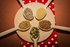 Semi sui cucchiai di legno che stanno trovando al tagliere rotondo ed al tovagliolo rosso - i semi del sesamo, del seme di lino,  Fotografia Stock
