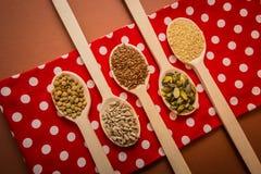 Semi sui cucchiai di legno che stanno trovando al tovagliolo rosso - i semi del sesamo, del seme di lino, della zucca e di giraso Fotografia Stock