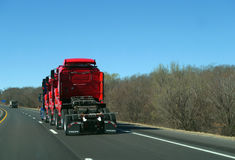 Semi tractor hauling three semi trucks, red, on highway stock photo