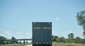 Disaster Response First Responders. A semi tractor trailer and first responders in route with water, clothing, food and other emergencies supplies to an area royalty free stock image