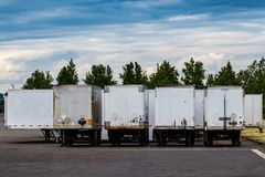 Semi tractor trailers parked in a row with doors closed under a blue cloudy sky. With trees Royalty Free Stock Photo