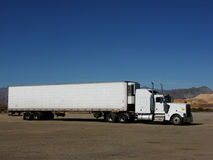 Semi Trailer in Desert. A plain white semi parked in the desert. Features loads of text space around this 18 wheeler. Great for driving school promotions Royalty Free Stock Photography