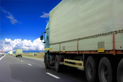Semi-trailer on highway. Rear side view of semi trailer on highway with blue sky and cloudscape in background Royalty Free Stock Image