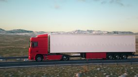 Semi-trailer truck driving along a desert road. A semi truck passes the camera driving on a highway into the sunset, side-view camera tracking and panning to stock footage