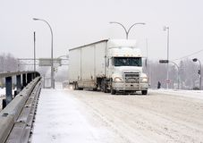 Semi trailer truck driving in winter snow storm. POINTE CLAIRE, QUEBEC/CANADA - DECEMBER 9, 2008 - Big rig attempts to cross overpass at St. John`s on icy road Royalty Free Stock Photo