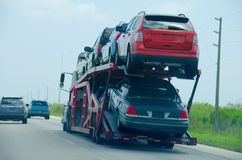Semi trailer truck hauling load of cars down road Royalty Free Stock Images