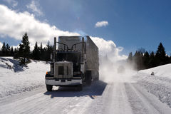 Semi-trailer Tuck On Icy Road. Big Rig and trailer driving down an icy and dangerous  road with snow blowing behind the truck on a cold clear day in the Royalty Free Stock Images