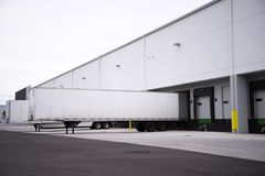 Semi trailers waiting loading and unloading in the dock of wareh. Long full-sized semi trailers stand it row at the dock gates of a large industrial warehouse Royalty Free Stock Image