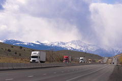 Semi tricks convoy on devided highway on hills snowy mountains Royalty Free Stock Image