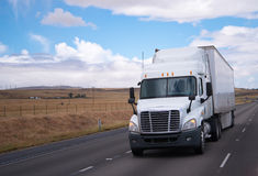 Semi truck big rig on road with meadow background Royalty Free Stock Images