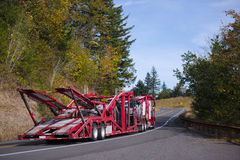 Semi Truck Car Hauler Red trailer on autumn winding road. Big rig Semi Truck Car Hauler with red specialized trailer for transportation several cars moving on a royalty free stock photography