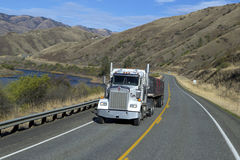 SEMI TRUCK DRIVING ON MOUNTAIN HIGHWAY Royalty Free Stock Photo