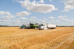 Semi truck and farm machinery parked in a field at harvest Royalty Free Stock Photos