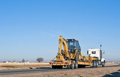 Semi-truck hauling a back-hoe loader combination. Big truck with a drop-deck trailer hauling a back-hoe tractor Royalty Free Stock Images
