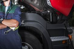 Semi Truck Mechanic Job. Caucasian Truck Service Technician with the Iron Wrench. Vehicle Maintenance Concept stock photos