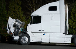 Semi truck with open hood and engine repairs. Powerful modern white semi-truck with the open hood standing evening on parking lot. The hot engine needs to be Royalty Free Stock Photo