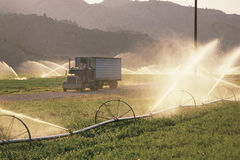 Semi Truck passing irrigation fields Stock Photos