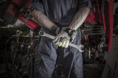 Semi Truck Pro Mechanic. Caucasian Service Worker with Heavy Duty Wrench Preparing For Complicated Truck Fix royalty free stock photography