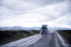 Semi-truck in raining dust on wet interstate road Stock Images