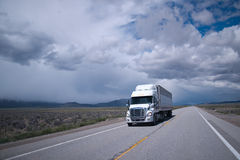 Semi truck with reefer trailer on flat long Arizona road royalty free stock images